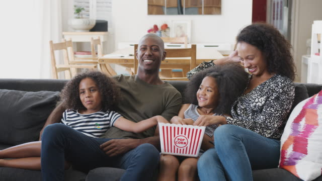 Family Sitting On Sofa At Home Eating Popcorn And Watching Movie Together Family sitting on sofa watching movie at home and eating popcorn - shot in slow motion family watching tv stock videos & royalty-free footage