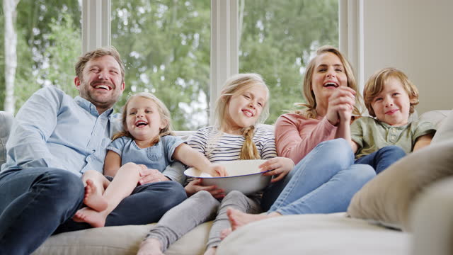 Family Sitting On Sofa At Home Laughing And Watching TV With Popcorn Together video