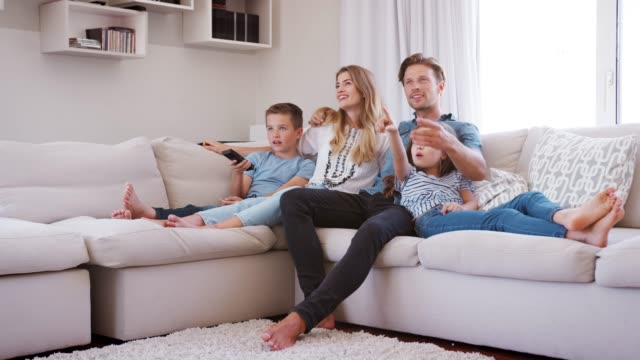 Family Sitting On Sofa At Home Watching TV Together Slow motion sequence of family relaxing on sofa at home together and watching television living room stock videos & royalty-free footage