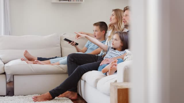 Family Sitting On Sofa At Home Watching TV Together Slow motion sequence of family relaxing on sofa at home together and watching television family watching tv stock videos & royalty-free footage