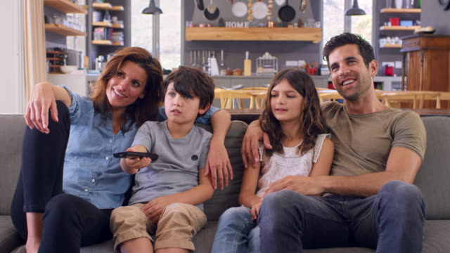 Family Sitting On Sofa In Open Plan Lounge Watching Television Slow motion sequence of family sitting on sofa in lounge watching television together family watching tv stock videos & royalty-free footage
