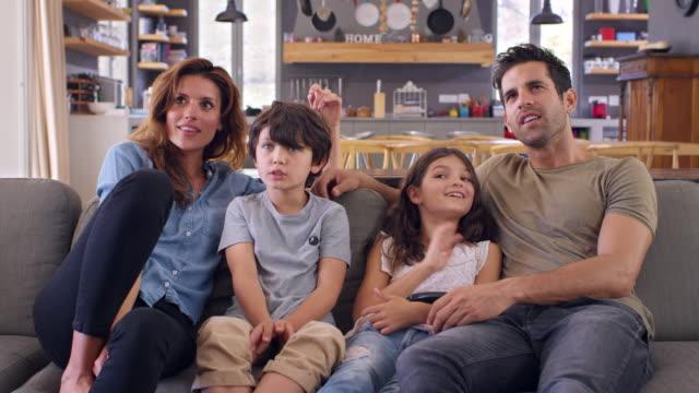 vídeos y material grabado en eventos de stock de familia sentado en el sofá en el salón de planta abierta viendo la televisión - family watching tv