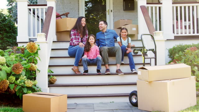 vídeos de stock e filmes b-roll de family sitting on steps of new home on moving in day - transferência