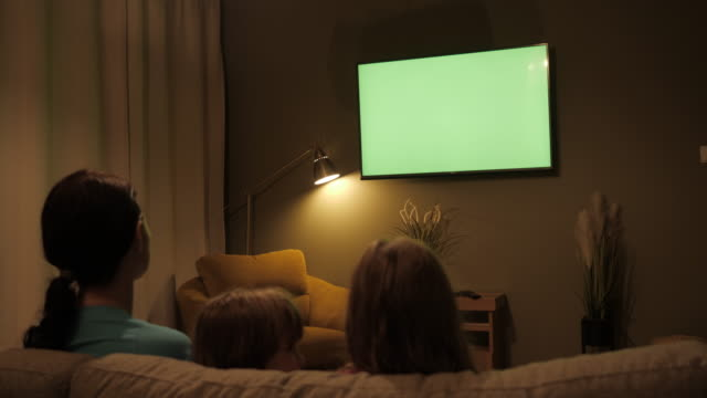 vídeos de stock e filmes b-roll de family sitting together sofa in their living room night watching tv green screen. rear view of family with children sitting on sofa in living room evening watching green mock-up screen tv together. - tv e familia e ecrã