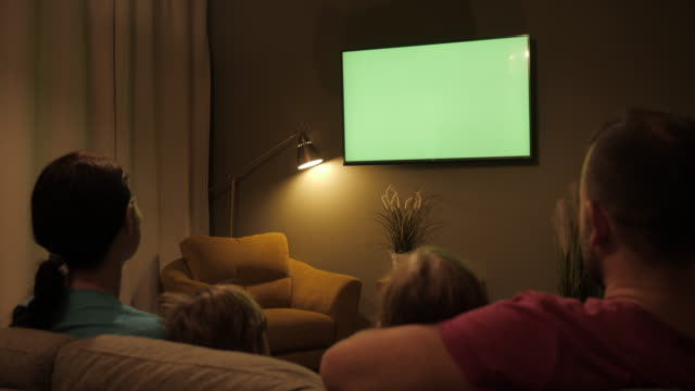 Family Sitting Together Sofa In Their Living Room Night Watching TV Green Screen. Rear View Of Family With Children Sitting On Sofa In Living Room Evening Watching Green Mock-up Screen TV Together. Family Sitting Together Sofa In Their Living Room Night Watching TV Green Screen. Rear View Of Family With Children Sitting On Sofa In Living Room Evening Watching Green Mock-up Screen TV Together. family watching tv stock videos & royalty-free footage