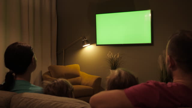 family sitting together sofa in their living room night watching tv green screen. rear view of family with children sitting on sofa in living room evening watching green mock-up screen tv together. - television industry stock videos & royalty-free footage