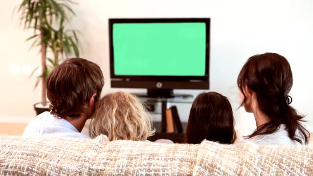 vídeos y material grabado en eventos de stock de familia sala de estar mientras ve su programa favorito en el televisor - family watching tv