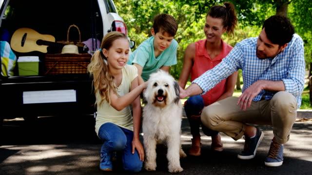 家族は、公園でその犬と座って ビデオ
