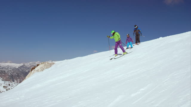 PAN Family skiing down the slope on a sunny day video