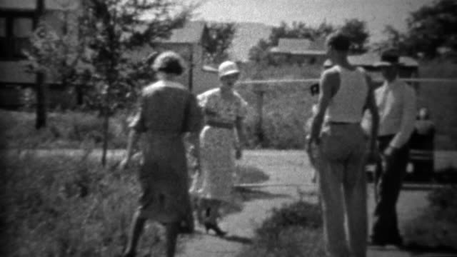 1934: Family skipping towards camera in front of Ford model A car. video