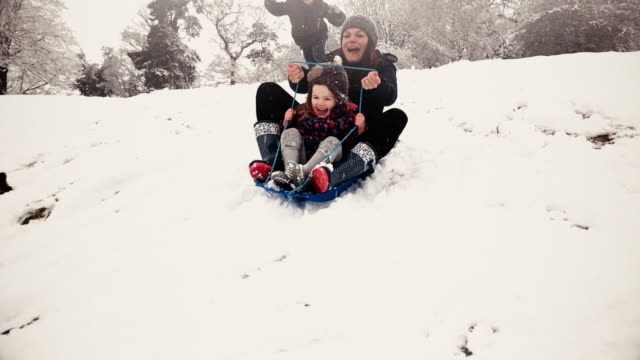vídeos de stock e filmes b-roll de family sledging down a snowy hill during the christmas holidays - family christmas