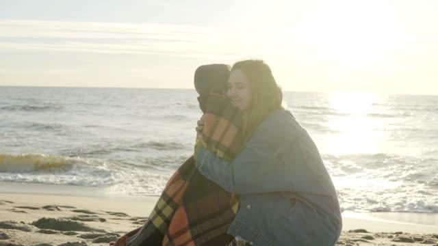familie zeit im sonnigen tag am sandstrand zu verbringen. mutter umarmt hatte hält auf ihren niedlichen kleinen sohn. glückliche zeit zusammen - ostsee stock-videos und b-roll-filmmaterial