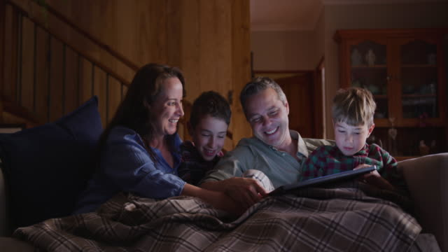 Family spending time together at home in the evening Front view of a Caucasian couple and their two young sons at home in the living room in the evening, sitting on a sofa together under a blanket, looking at a laptop computer and smiling, slow motion blanket stock videos & royalty-free footage