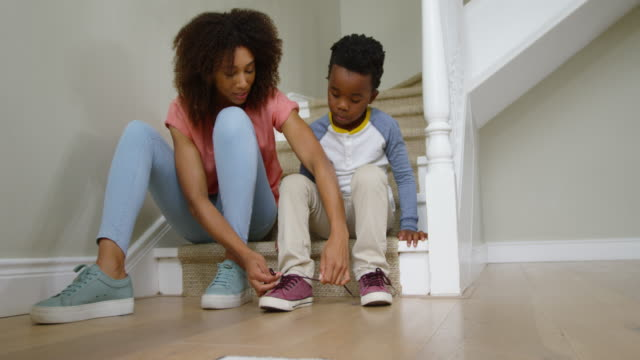 Family spending time together at home Front view of an african american mother and her young son sitting on the stairs in the hallway at home, the mother tying the shoelaces on his shoe, slow motion shoe stock videos & royalty-free footage
