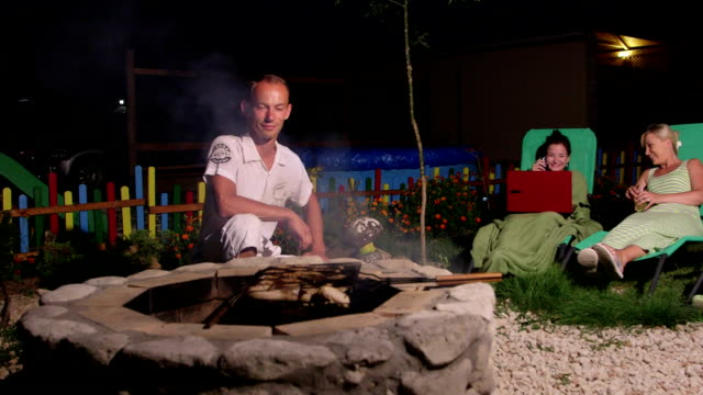 Family spending weekend in backyard near stone fire pit father grilling barbecue video