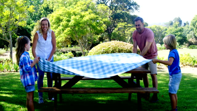 family spreading the tablecloth on picnic table 4k - picnic video stock e b–roll