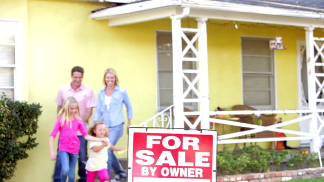 Family Standing By For Sale Sign Outside Home video