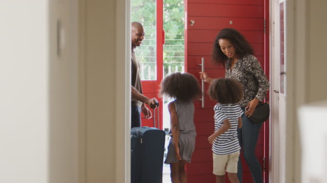 Family Standing By Front Door With Suitcase About To Leave For Vacation