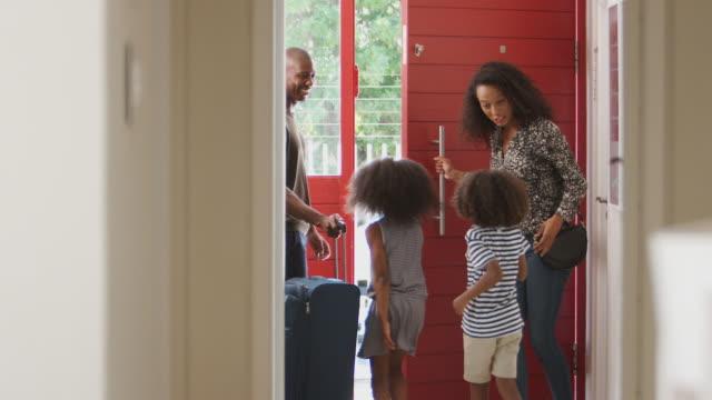 vídeos y material grabado en eventos de stock de familia de pie por puerta delantera con maleta a punto de salir para vacaciones - despedida