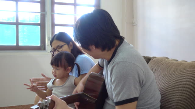 Family Tableau, Family singing together with father playing the guitar video