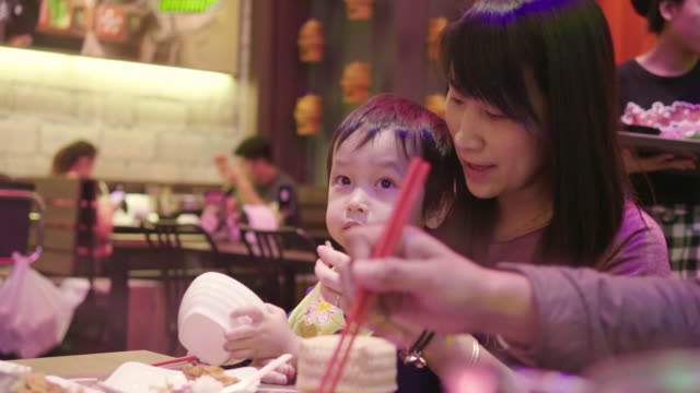 Family Tableau of Thai family are eating sukiyaki and thai food at the restaurant video