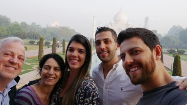 Family taking a selfie of Taj Mahal, India Family taking a selfie of Taj Mahal, India cousin stock videos & royalty-free footage