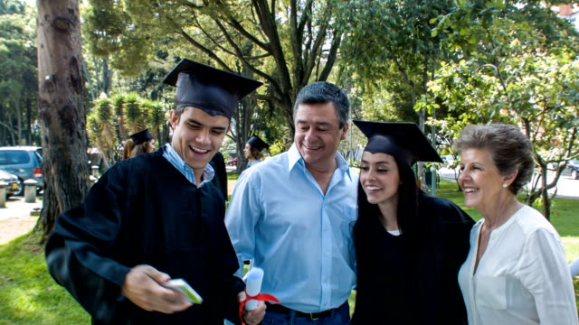 Famille prenant un selfie le jour de la remise des diplômes - Vidéo
