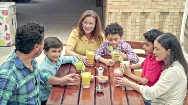 familie macht ein selfie beim safttrinken im restaurant - lateinische schrift stock-videos und b-roll-filmmaterial