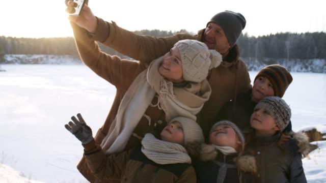 vídeos y material grabado en eventos de stock de familia tomando selfies en winter woodland - memorial day weekend