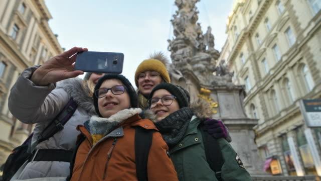 Family taking selfies near Vienna Plague Column in Vienna, Austria