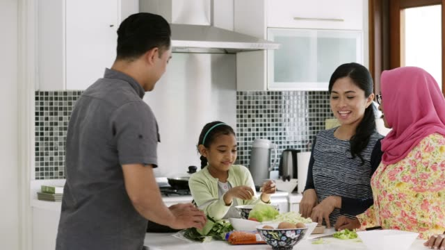 family talking while standing at kitchen island - etnia malese video stock e b–roll