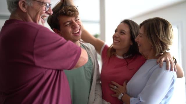 家庭でティーンエイジャーの少年をからかい家族 - 親族会点の映像素材/bロール
