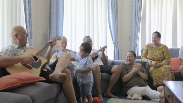 Family Time Is My Favourite Wide shot of Pacific Islander multi-generation family sitting together at home. The father is playing a guitar and the son is playing the ukulele. minority groups stock videos & royalty-free footage