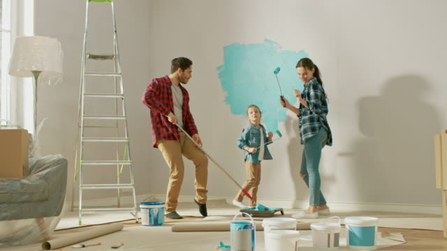Family Time Together with Small Daughter. Young Father and Mother are Dancing and Fooling Around with Paint Rollers. Wall Paint Color is Light Blue. Room at Home is Prepared for Renovations.