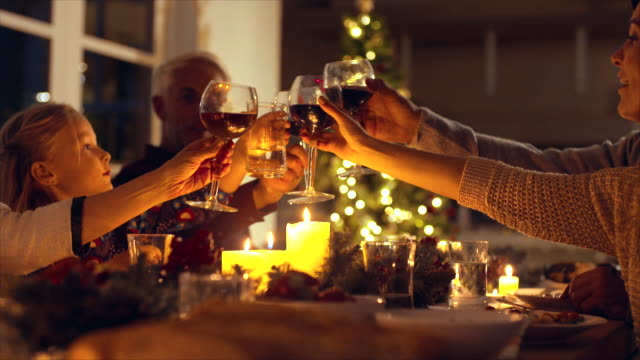family toasting wine at christmas dinner - cena di natale video stock e b–roll