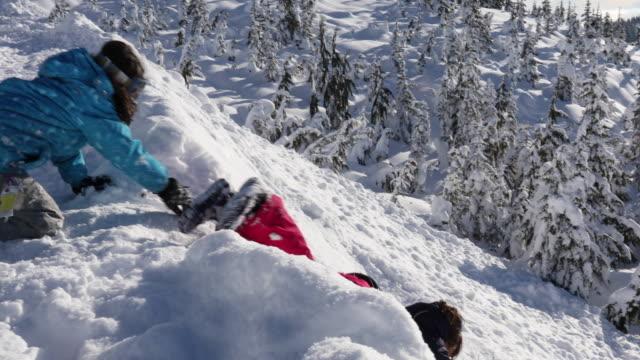 Tobogán familiar abajo de cuesta empinada de nieve, hacia los árboles - vídeo