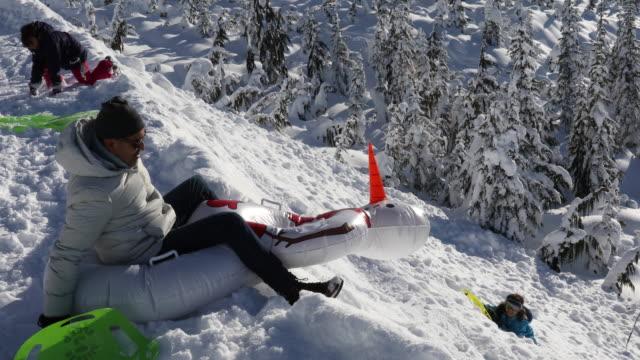 Family toboggan down steep snow slope, towards trees