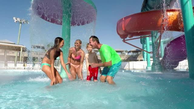 Family, two children having fun at water park splashing video