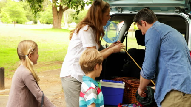 family unloading their car for a camping trip - picnic stock videos and b-roll footage