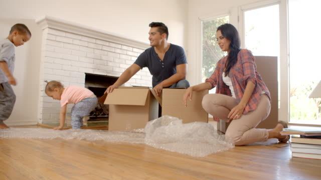 familj uppackning lådor i nytt hem på rörliga day - flyttlådor bildbanksvideor och videomaterial från bakom kulisserna