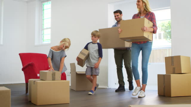 family unpacking boxes in new home on moving day - new home stock videos & royalty-free footage