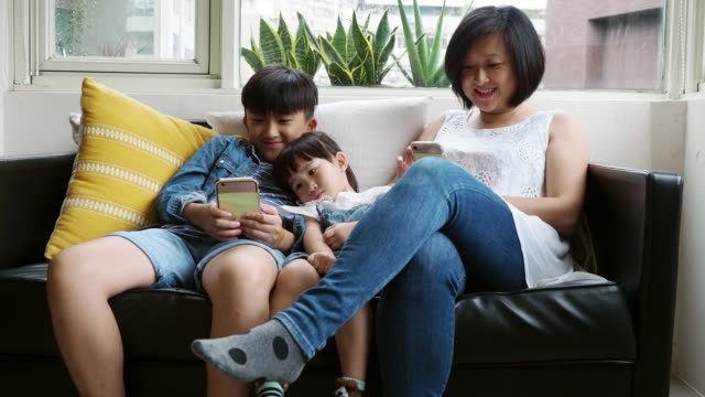 Family using a mobile phone together sitting on the sofa at home video