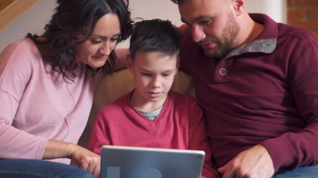 Family using digital tablet at home video