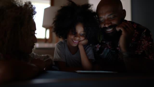 семья, используя цифровой планшет в домашних условиях - уютный стоковые видео и кадры b-roll