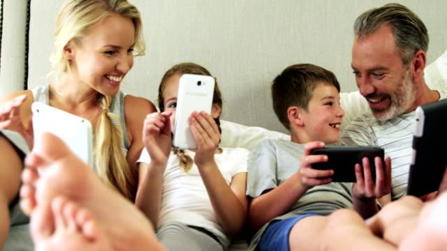 Familie mit Hilfe von elektronischen Geräten im Schlafzimmer zu Hause 4k – Video