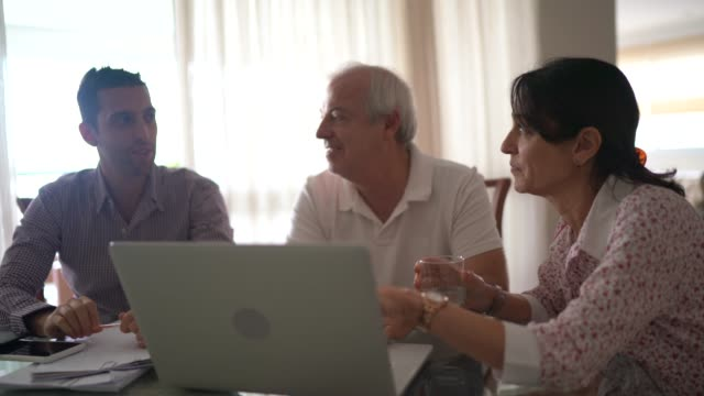 Family using laptop at living room Family using laptop at living room baby boomers stock videos & royalty-free footage