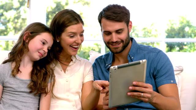 vídeos y material grabado en eventos de stock de familia usando tableta en la sala de estar - 20 24 años