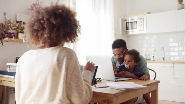 familj som använder teknik när de sitter vid bordet - enbarnsfamilj bildbanksvideor och videomaterial från bakom kulisserna