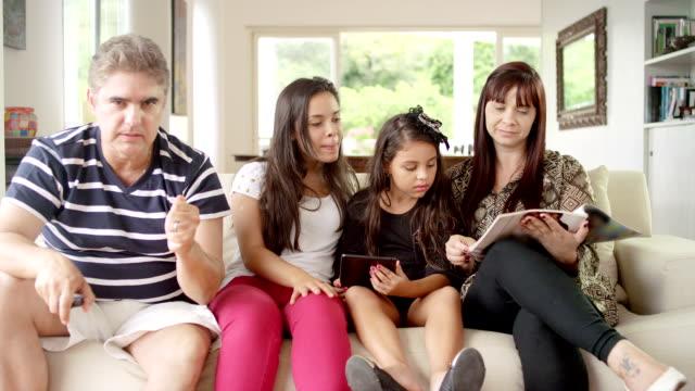 vídeos de stock e filmes b-roll de família utilizando tecnologia juntos na sala de estar - tv e familia e ecrã