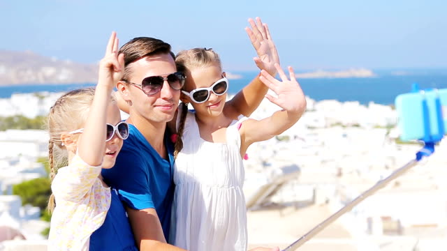 Family vacation in Europe. Father and kids taking selfie background Mykonos town in Greece video